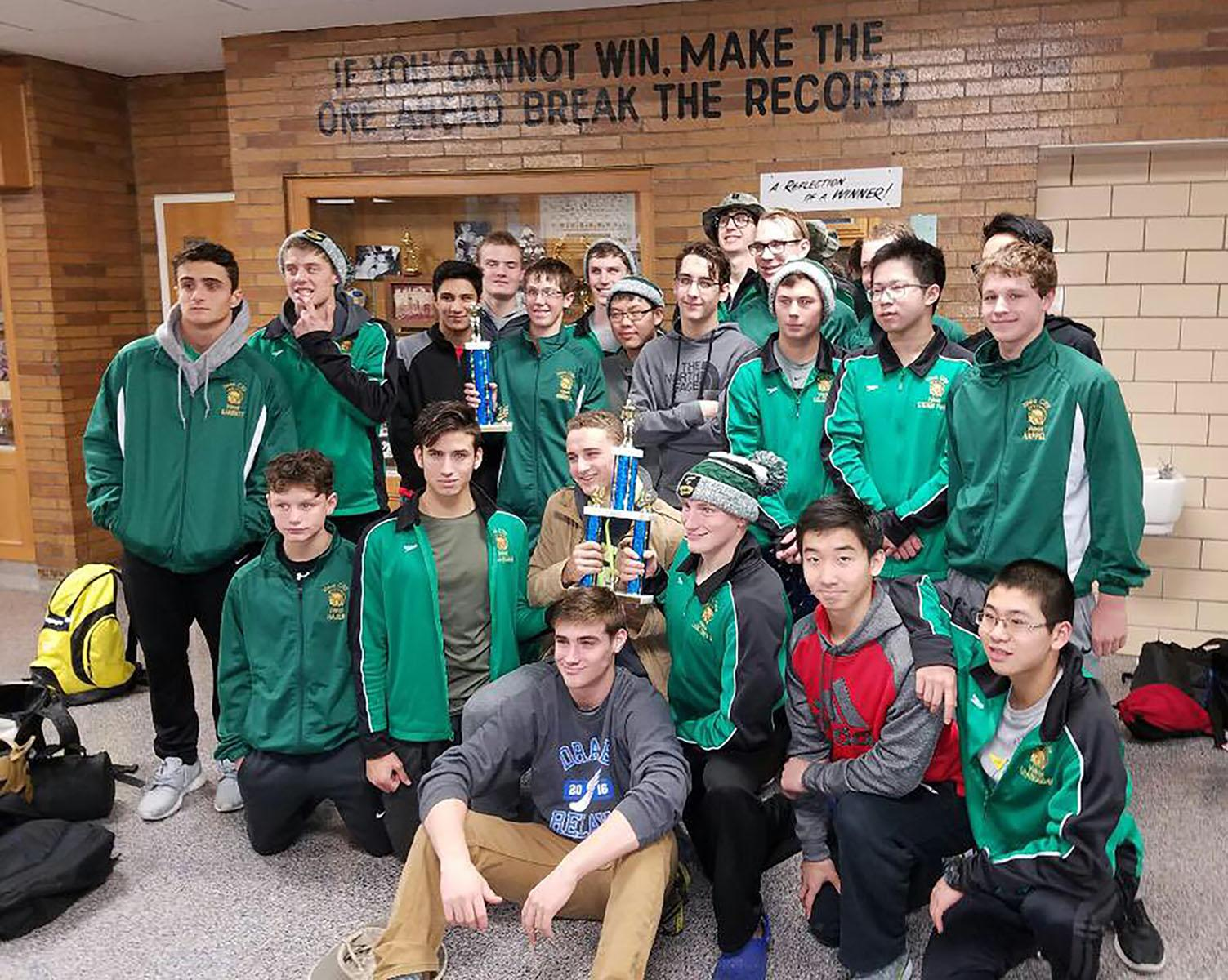 The boys swim team poses with their trophies at Cedar Rapids Jefferson. The Trojans won the J-Hawk relays, placing first in all varsity events.