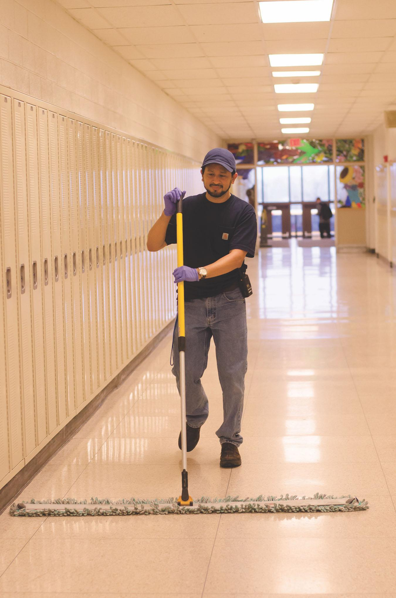 Carlos mopping the art hallway. Photo by Sarah Longmire