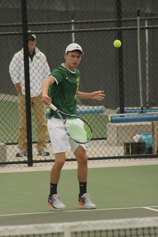 Senior Cole Schneider hits the tennis ball back to a player from Linn-Mar.