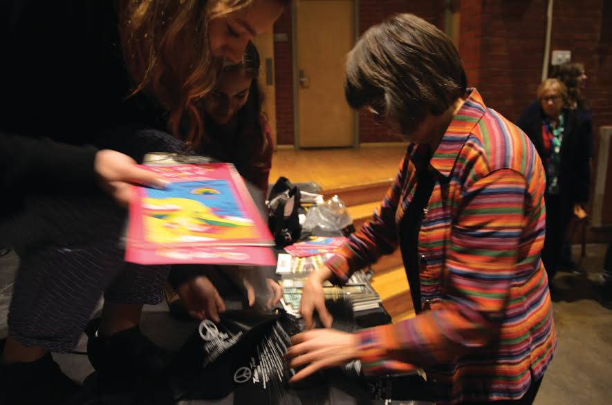 Mary Beth Tinker hands out coloring book and black arm bands to students at North Des Moines High School this past Thursday, Dec. 16 to celebrate the 50th anniversary of her middle school suspension that sparked the Supreme Court case Tinker v. Des Moines.