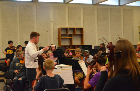 Welch conducts the concert orchestra while they work on their exercise book.