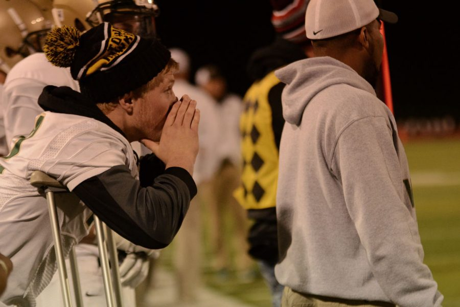 Injured player Tyler Yoerger `17 encourages his teammates from the sidelines on their way to defeating, Linn-Mar 50-7.