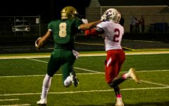 Oliver Martin '17 pushes off a defender as a runs towards the end zone