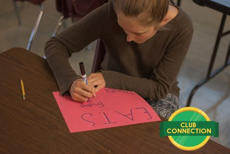 Club leader Mara Jensen creates posters to hang around the school advertising the club.