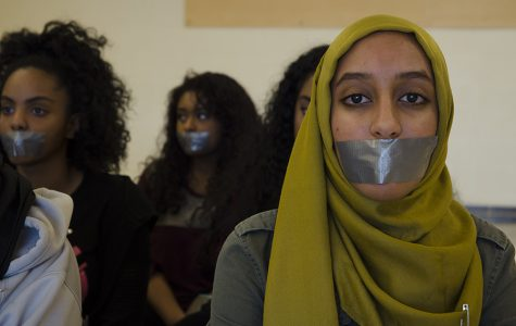 Sitting in silence, Raneem Hamad '17 wears a safety pin on her hijab.