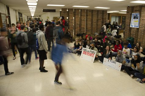 A student watches the sit-in after school in the flooded hallways.