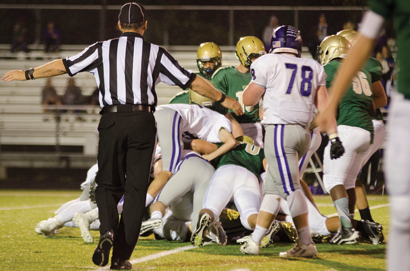 A football official breaks up a dog pile during the West-Burlington game