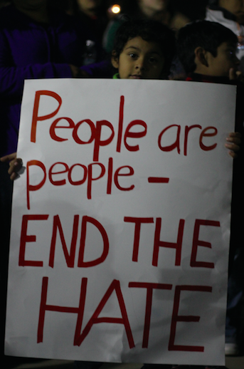 A protester holds an anti-hate sign.