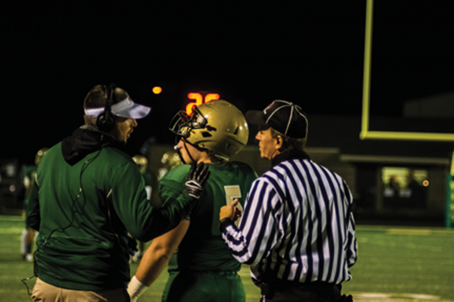 A referee talks to Breyton McDole `17 and a football coach during the home football game against Ottumwa on Oct. 21.