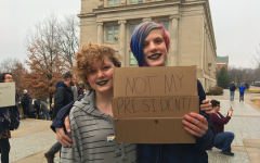 Junior high students Maddie and Lucy hold a sign to show what's on their minds.