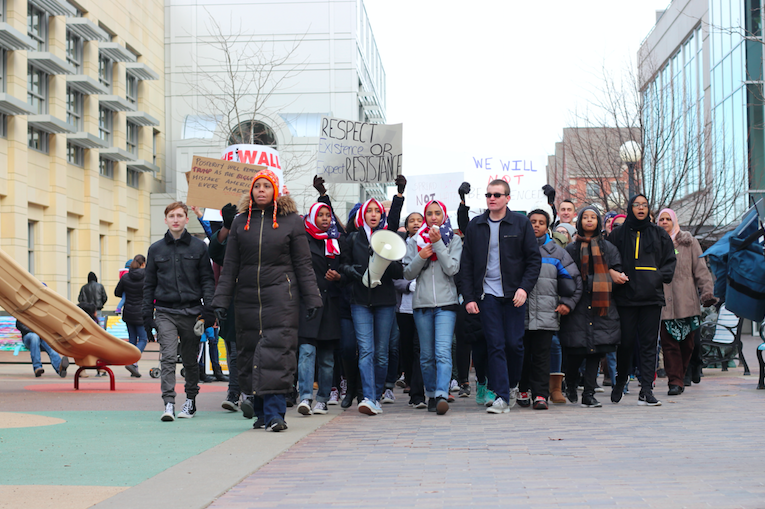 The post-rally march, led by West students, crosses the pedestrian mall by the library playground.