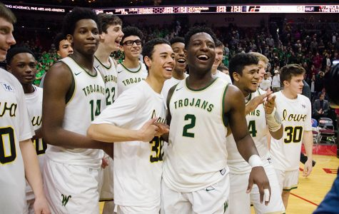 After winning 57-51 in the 4a state quarterfinals against Newton High School, the boys basketball team celebrates their progression through the state tournament at Wells Fargo Arena, Wednesday Mar. 8. The Trojans later advanced to play Kennedy High School in the state semifinals, and won 61-37.