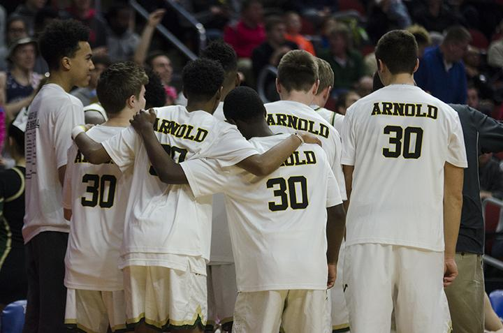 Arm in arm, the boys basketball team huddles up on the court at Wells Fargo Arena in the 4a state semifinal game against Cedar Rapids Kennedy on Friday Mar. 10.