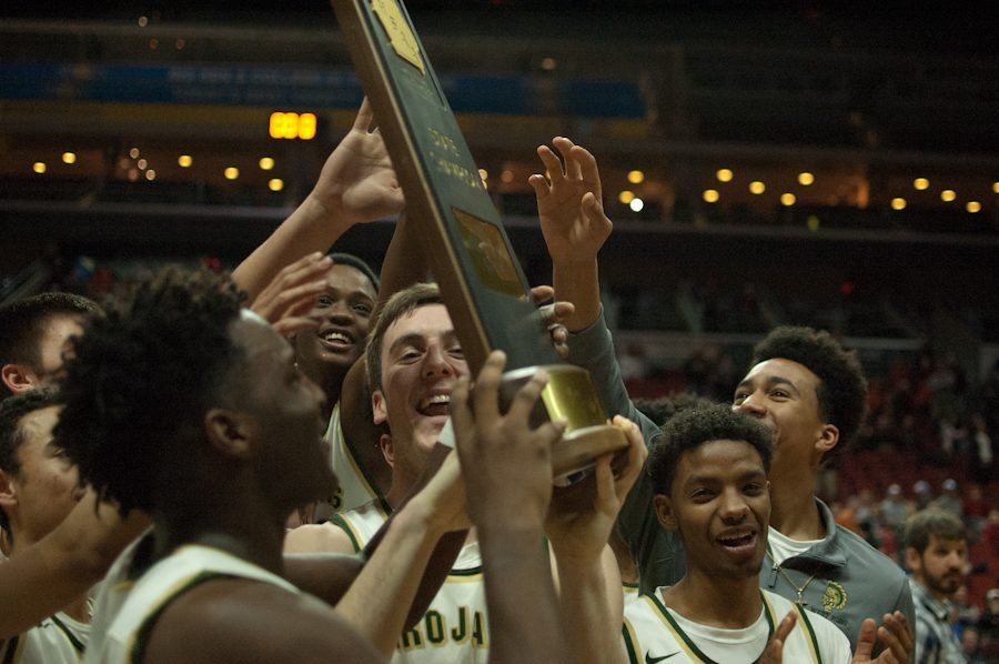 The varsity boys basketball team celebrates after receiving the 4A state championship trophy Saturday Mar. 11 at Wells Fargo Arena. After a loss to West Des Moines Valley in last year's championship game, the Trojans avenged their loss this year in a 64-50 victory for the team's seventh state title.