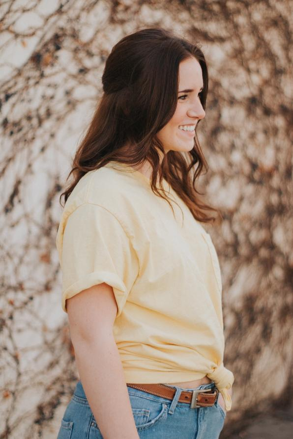 Lizzie+Burns+%2718+stands+in+front+of+the+old+vine+wall+downtown+in+her+bright+yellow+shirt+and+jeans.