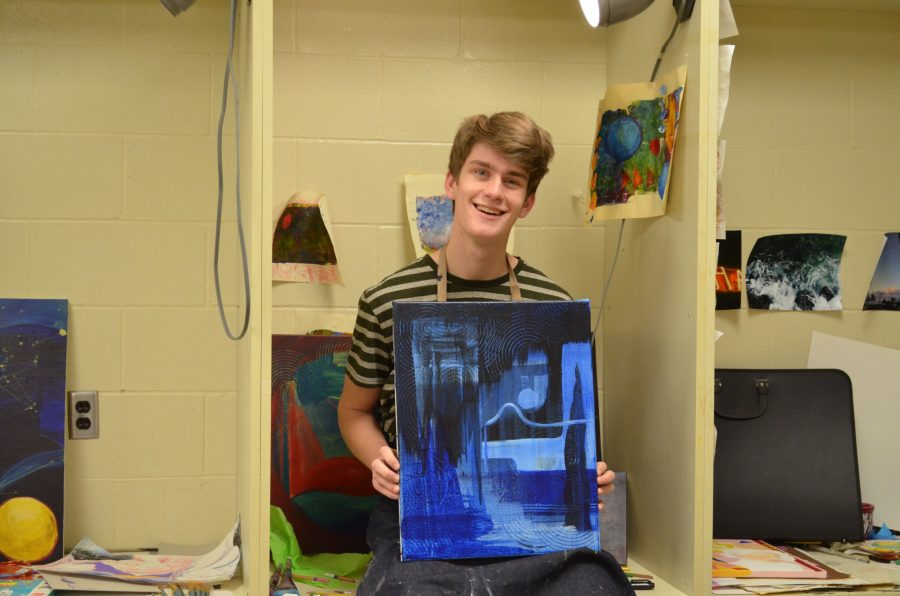 Micah Smith '17 holding one of his newer abstract pieces of art.