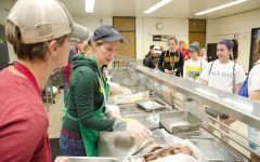 Volunteer Julie Peters prepares and serves a plate of pancakes, eggs and sausages as a part of the annual Booster Club Pancake Day for athletic funding in Iowa City Schools on Sat. April 8, 2017.