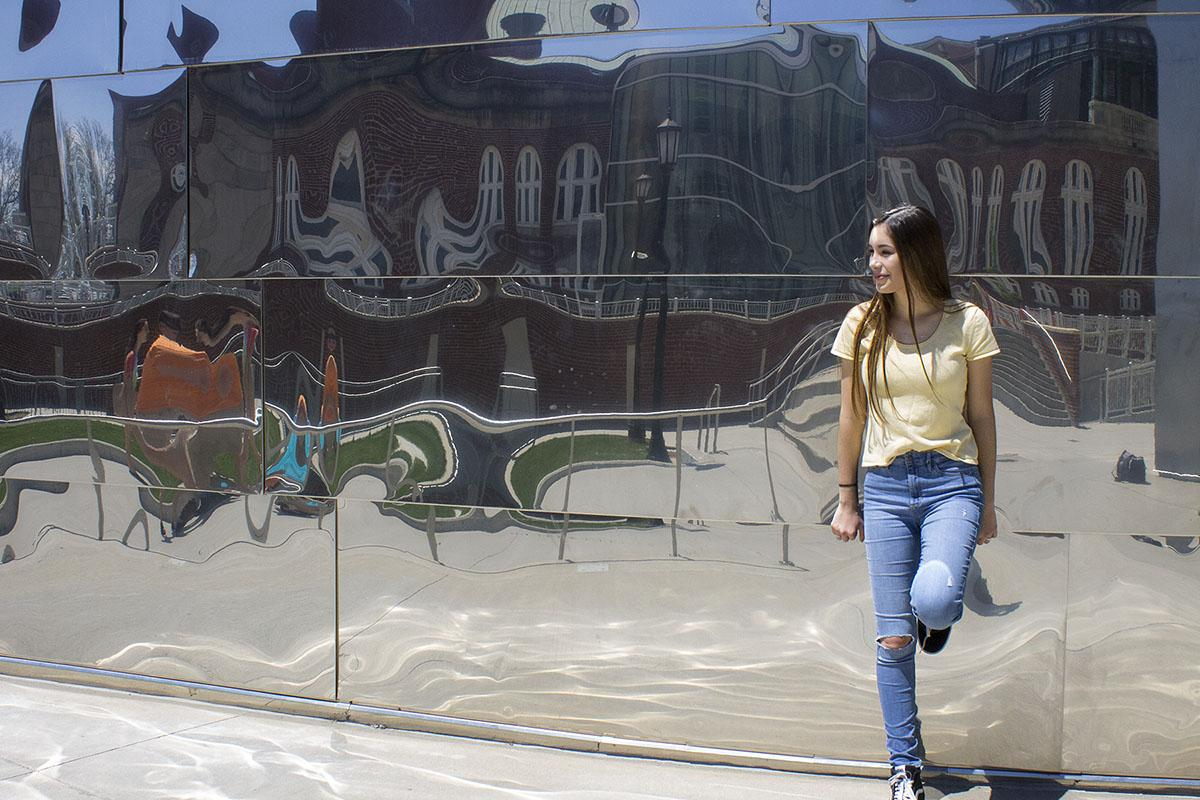Angela poses in front of a mirror building with skinny jeans, sneakers and a yellow shirt.