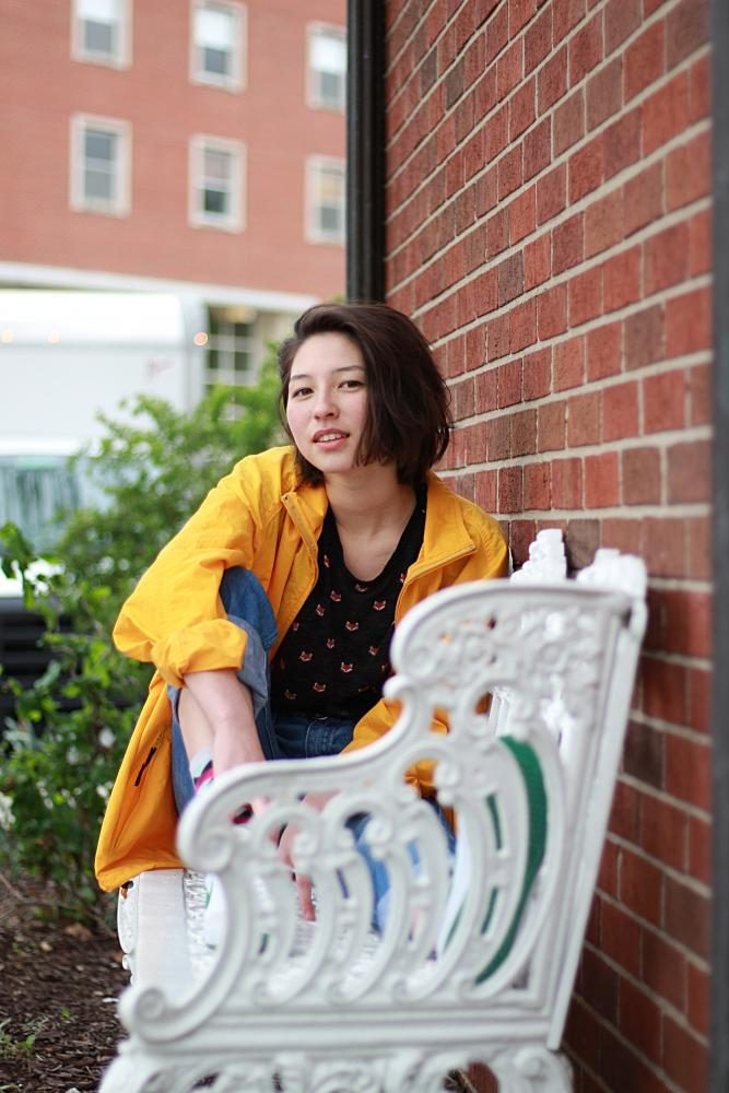 Angela Zirbes '18 models her simple spring outfit featuring high-waisted jeans and a rain jacket.