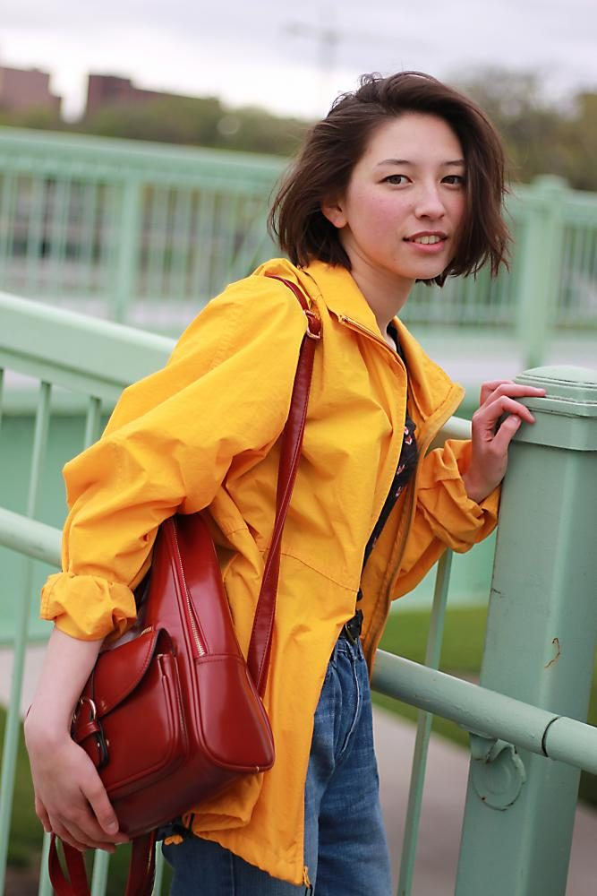 Angela Zirbes '18 models her favorite spring raincoat and red leather backpack in downtown Iowa City.