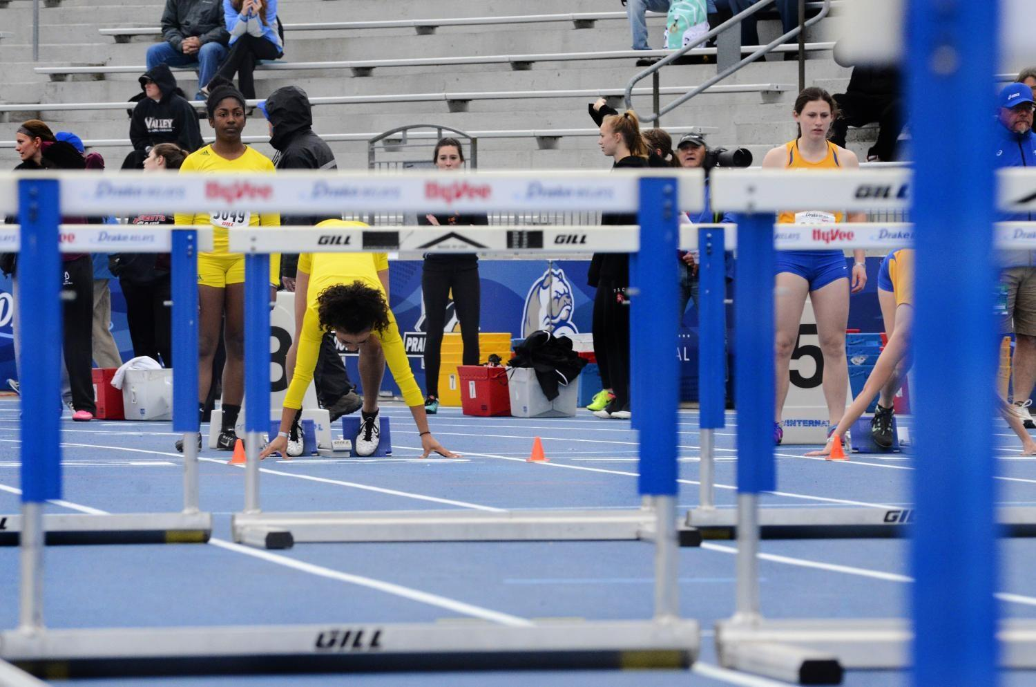Kitra Bell '18 sets up in her blocks for the girls shuttle hurdle relay on Saturday, May 29 at the Drake Relays. The girls placed second in the event, breaking the school record.