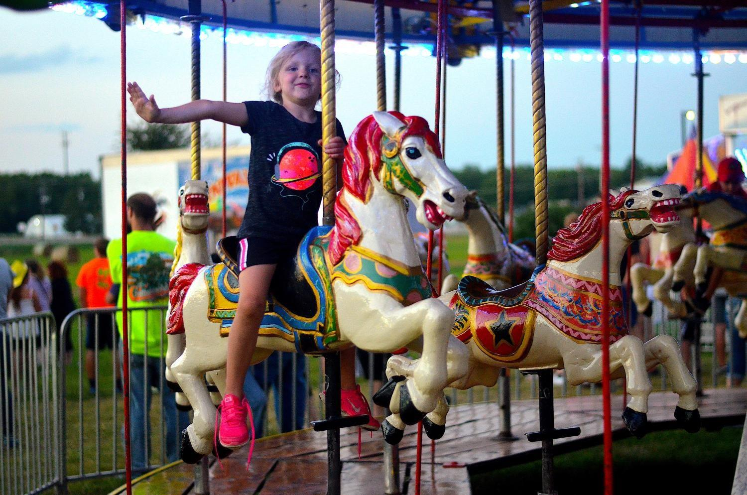 Imitating an airplane, a young girl rides the merry-go-round at the Johnson County Fair in Iowa City on July 27.