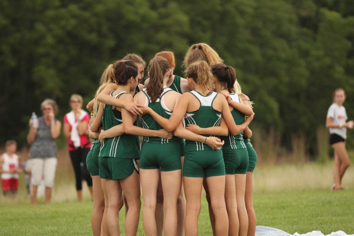 The girls varsity team huddles together before the race on Thursday, Aug. 24.