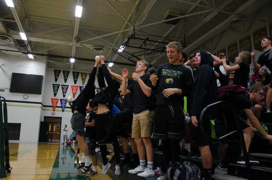 Members of the student section leap to catch the senior night volleyballs thrown by seniors before the game against Jefferson on Sept. 26.