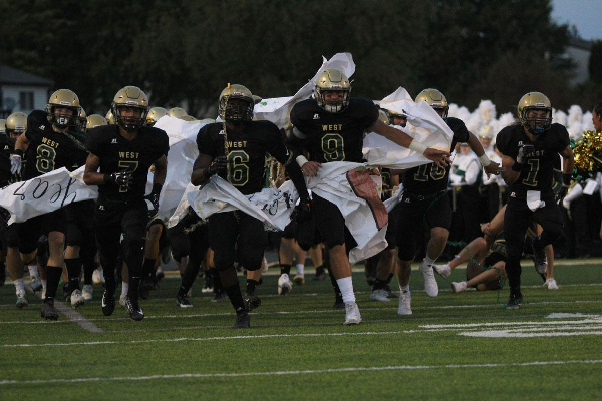The Trojans take the field, showing off their new all-black uniforms on Friday, Sep. 1.