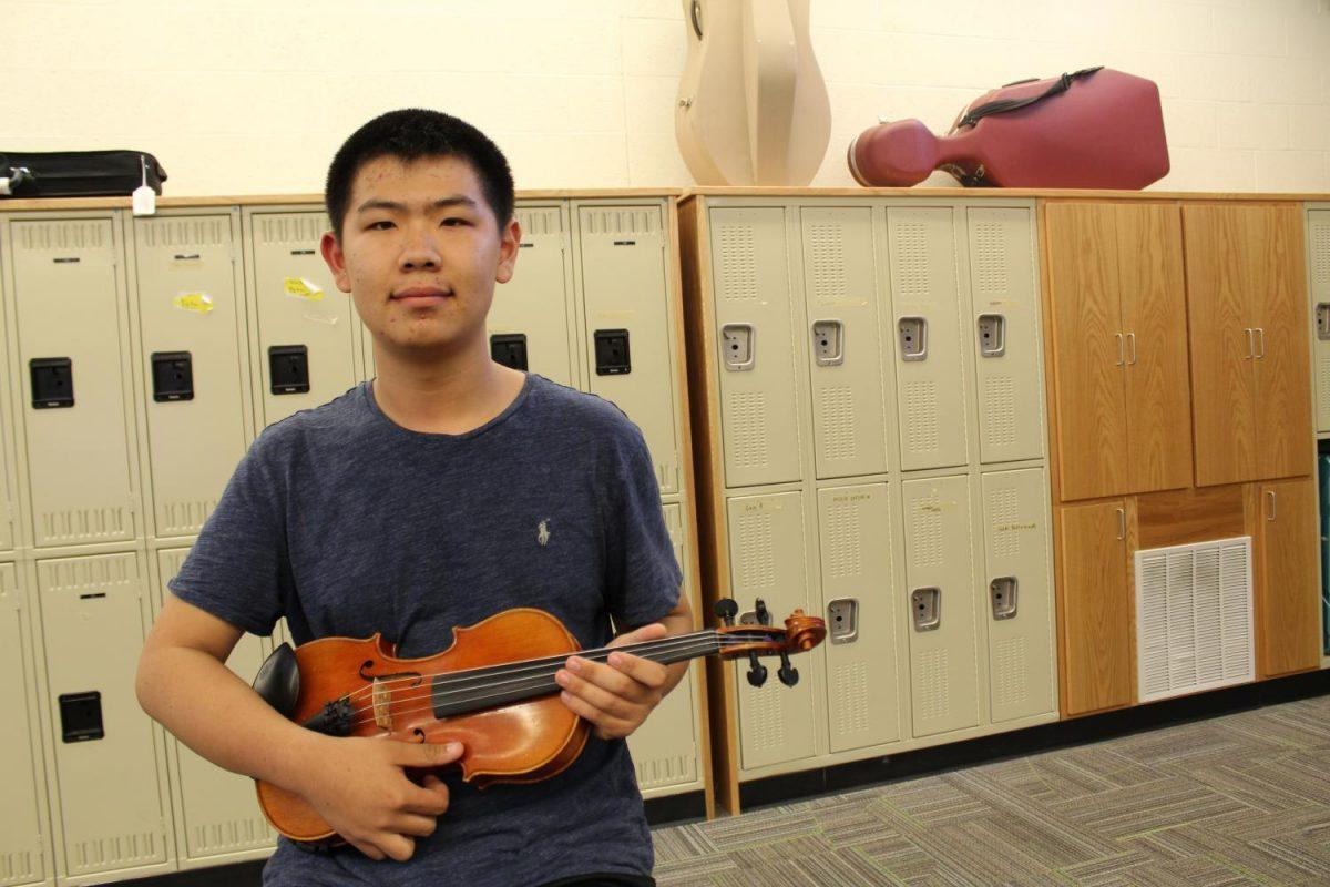 Justin Liu '19 displays his violin in the West High orchestra room