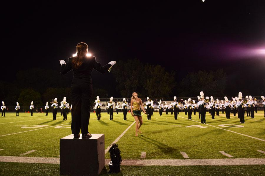Mady Nachtman 18 leads the marching band as Arielle Comellas 18 twirls her baton during the halftime performance.