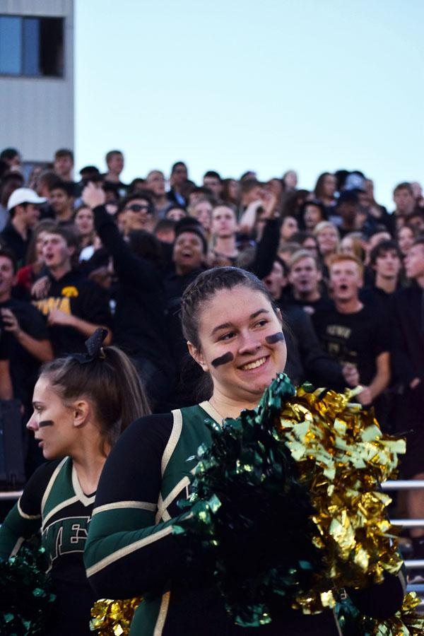 Ayanna Rost 19 cheers on the football team, as the student section roars in the background.