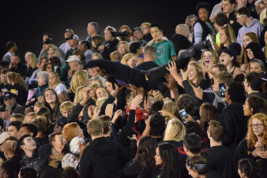 A West High student crowd surfs, making his way to the bottom of the student section.