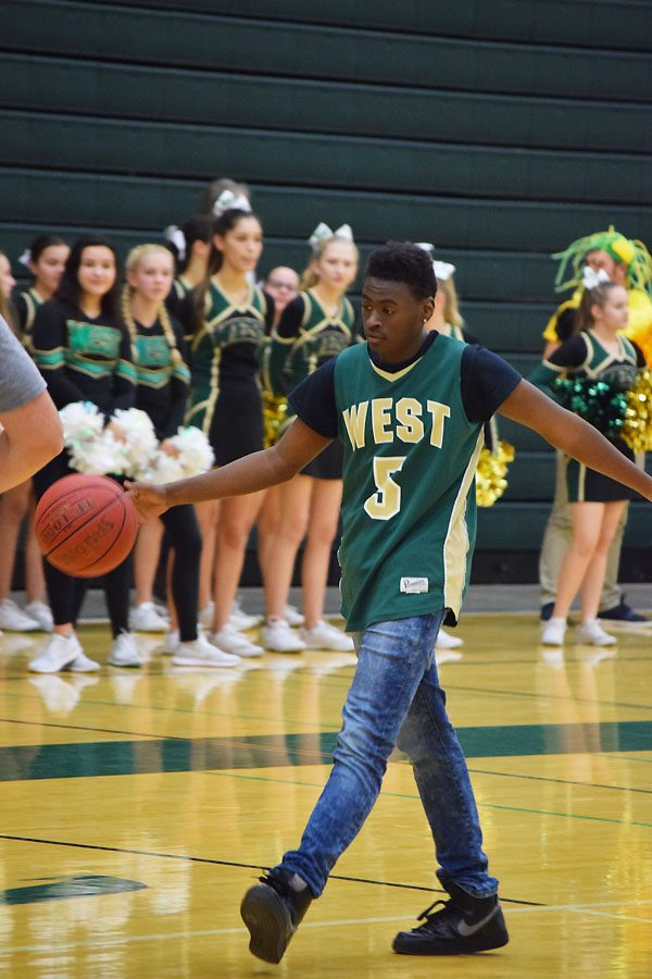 Quintin Jones 19 dribbles the basketball and will get ready to pass the ball to a Best Buddies member.