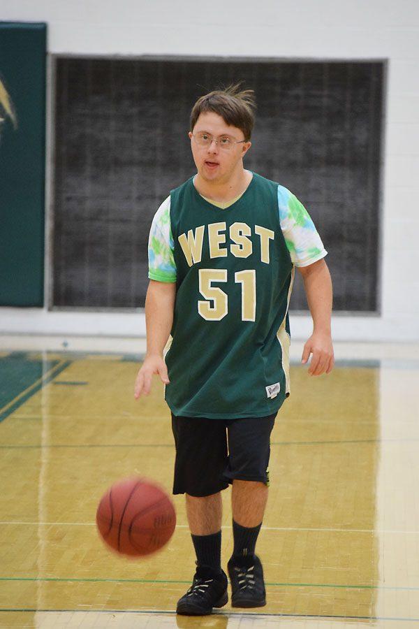 Ivan Cross 18 dribbles the basketball across the court.