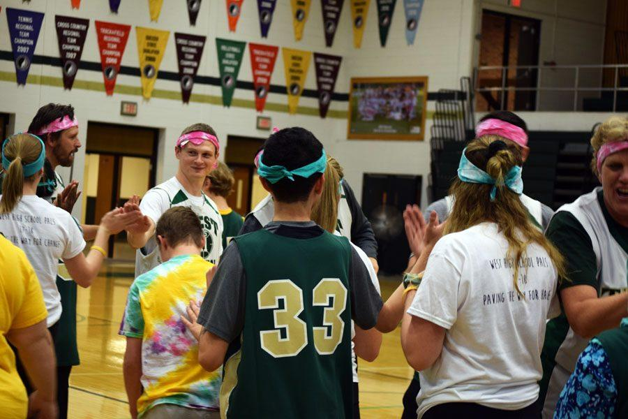 Best Buddies, PALs, and faculty high-five each other after the game.