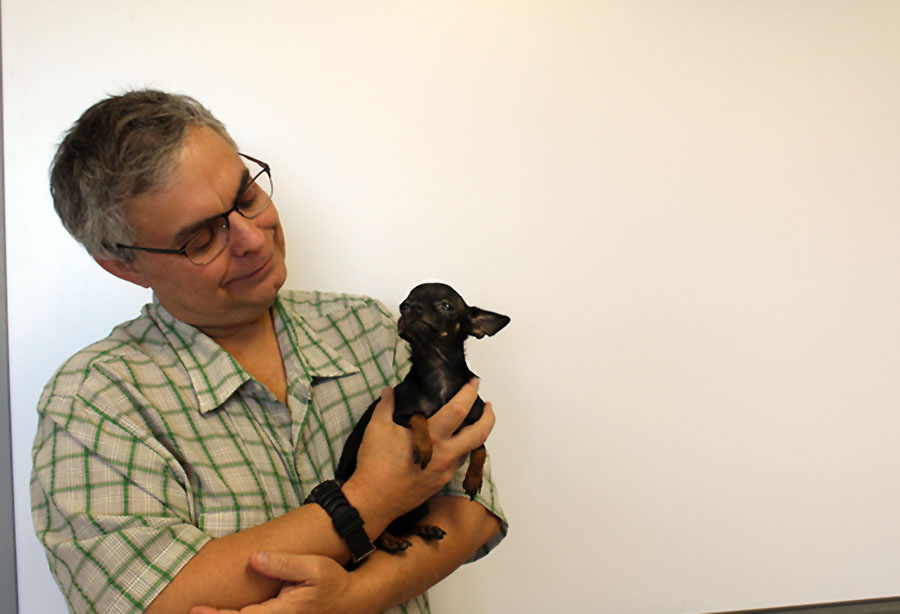Mr. Neuzil lovingly poses with one of his dogs, Orson.