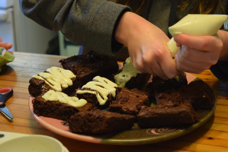 Staffers layer the mummy onto the brownie with white chocolate.