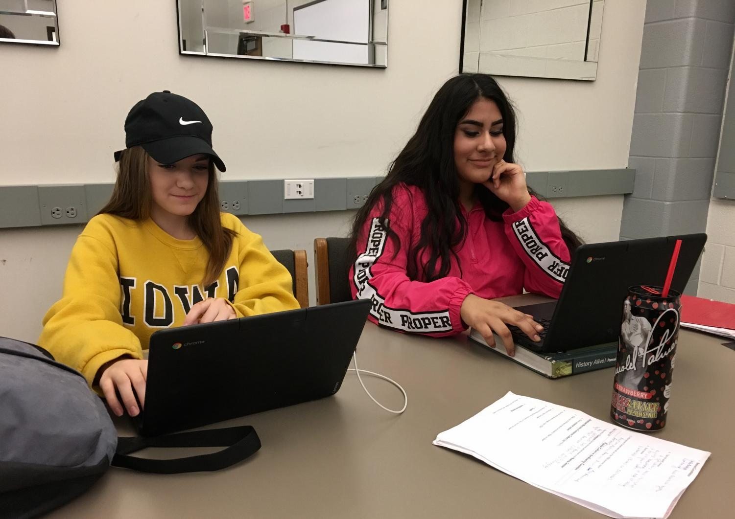 Courtney Mapel '21 and Lizette Perez '21 restart their Chromebooks after an accidental update by the district forced students to login every time they shut their laptop.