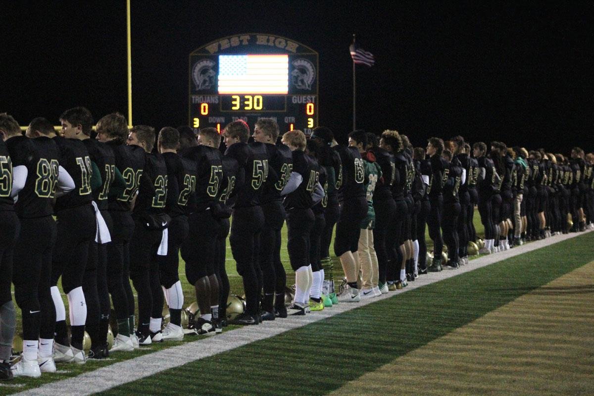 The football team stands together during the National Anthem on Friday, Oct. 27.