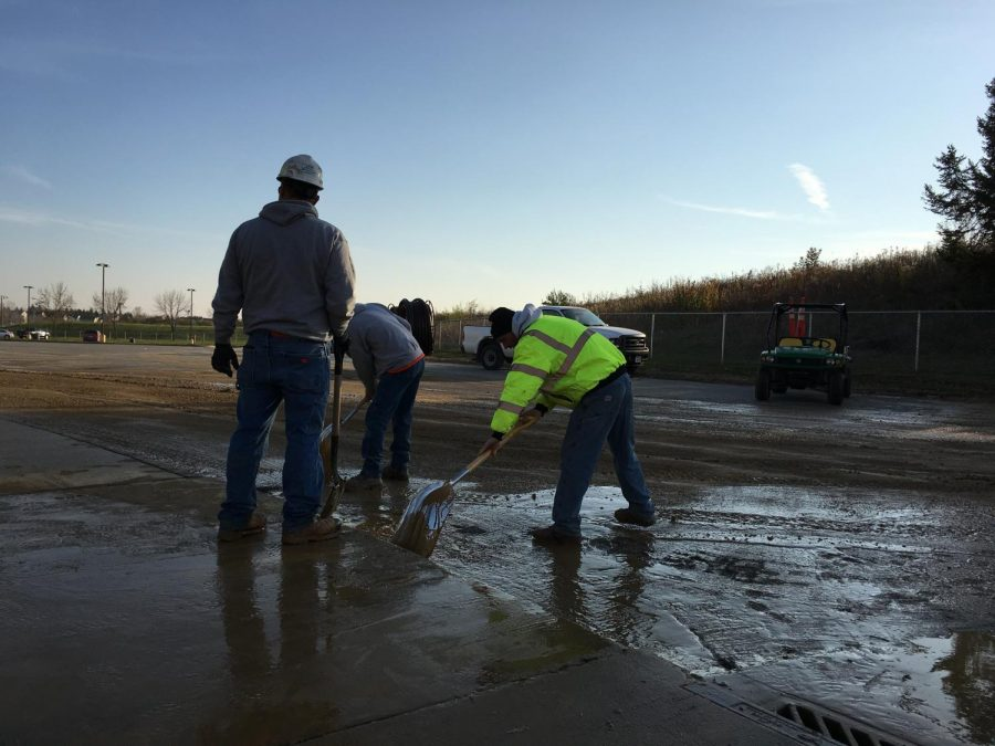 Construction workers scrape remaining water into nearby sewage drains.