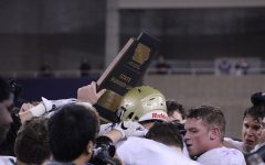 Dillon Doyle '18 lifts the state runner-up trophy up as the team gathers around it on Friday, Nov. 17.