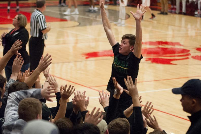 Austin Geasland '18 leads the student section in a cheer during the varsity basketball games against City on Dec. 12.