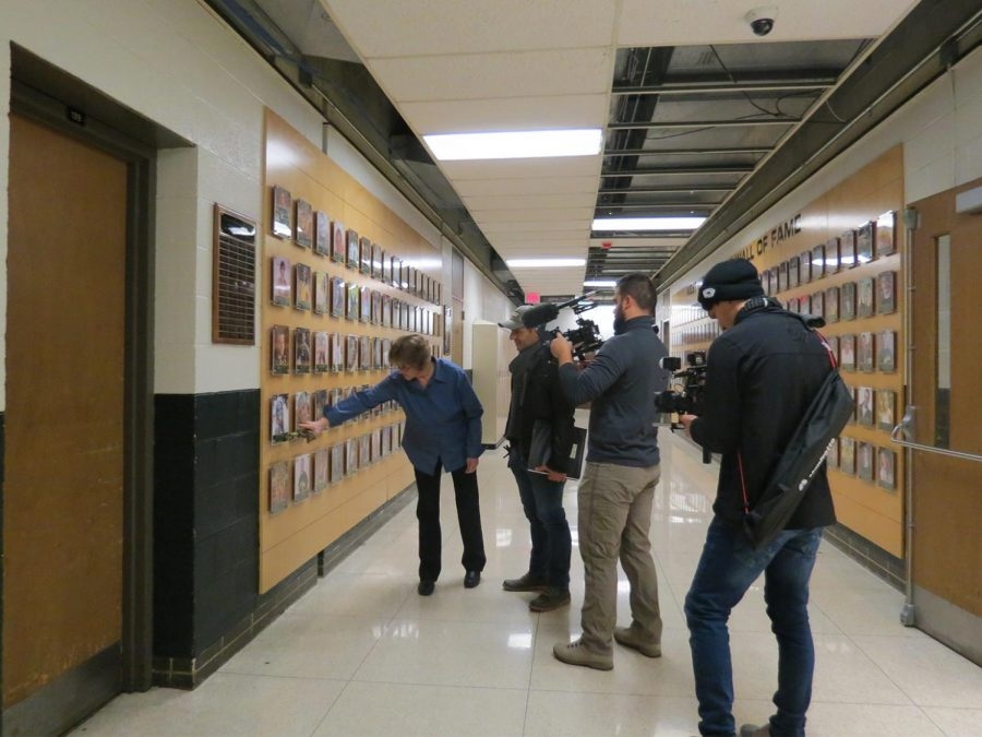 Kathy Bresnahan shows the West High Athletic Hall of fame to the camera crew and producer of