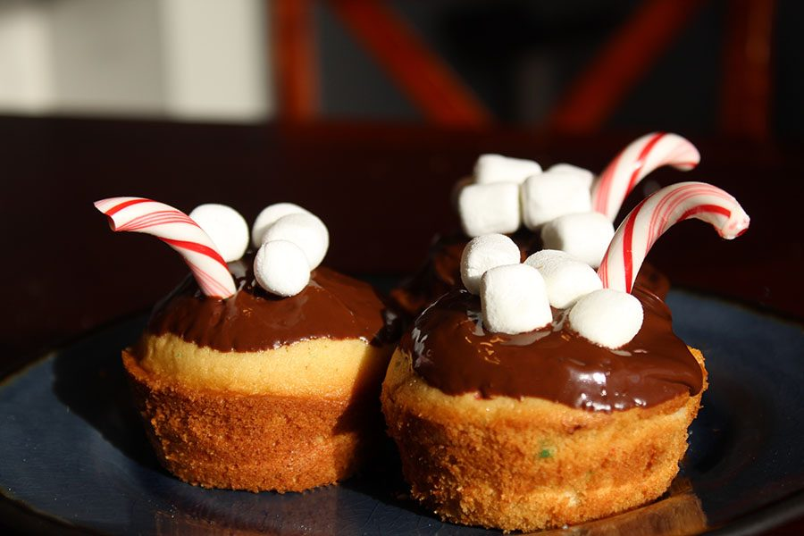 The completed muffins have been dipped into melted chocolate and decorated with mini marshmallows and candy canes.
