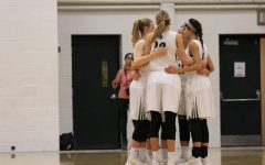Lauren Zacharias '19, Emma Koch '19, Logan Cook '18, Cailyn Morgan '19 and Rachael Saunders '18 huddle together at the beginning of the game on Tuesday, Jan. 23.