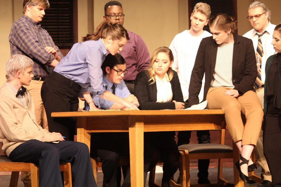 Characters huddle together to analyze sketch of the crime scene. From left to right: Cade Koch '18, Brandon Burkhardt '18, Meg Moreland '18, Sam Sunderland '19, Damarius Levi '18, Pieper Stence '18, Sean Harken '21. Paige Harken '18, Ethan Seylar '19 and Leah Brownsburger '18