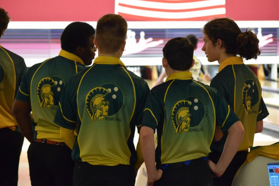 The boys bowling team huddles together and talks about their bowling strategies.