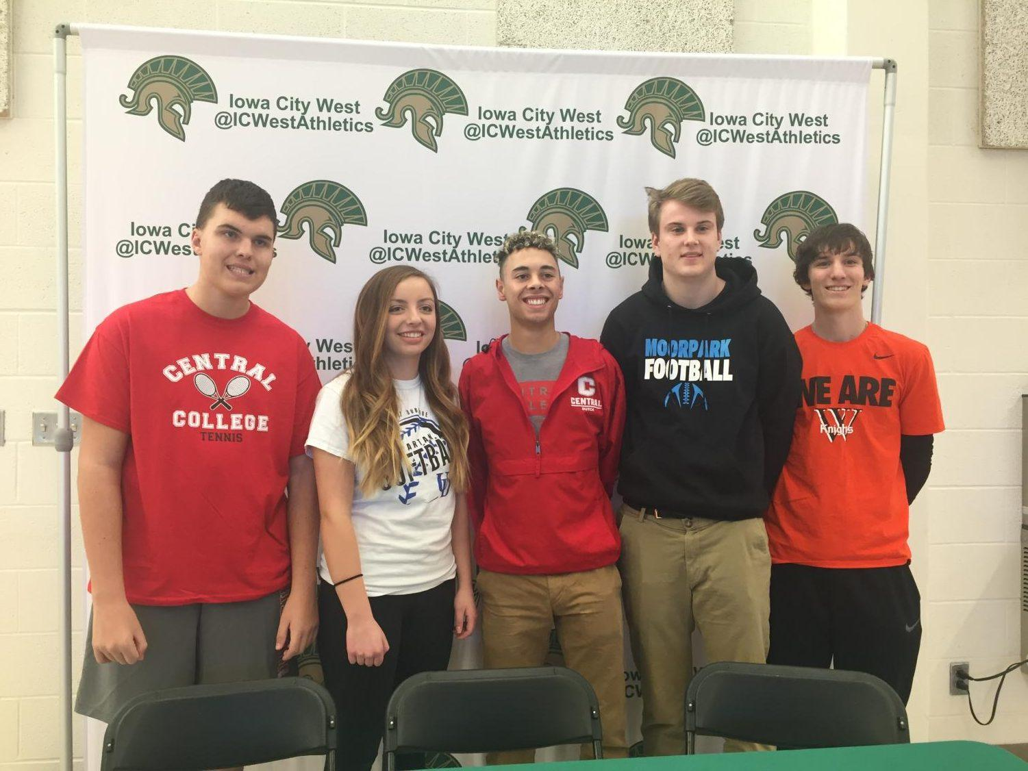 Students athletes stand together after signing to their schools.