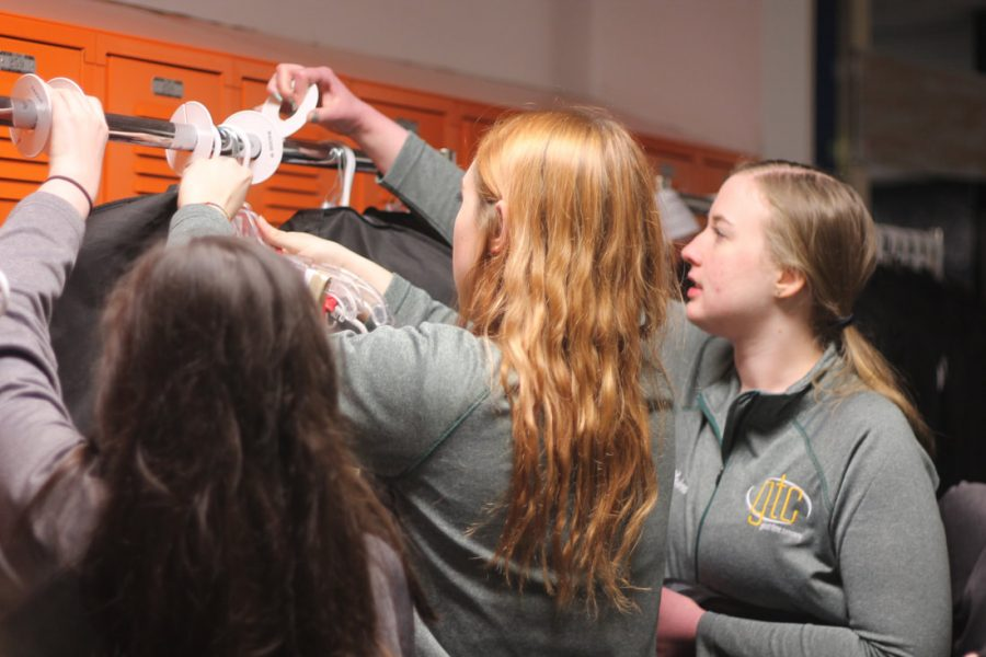 The show choir crew organizes costume racks at Benton's A Touch of Class.  (Lauren Ernst)
